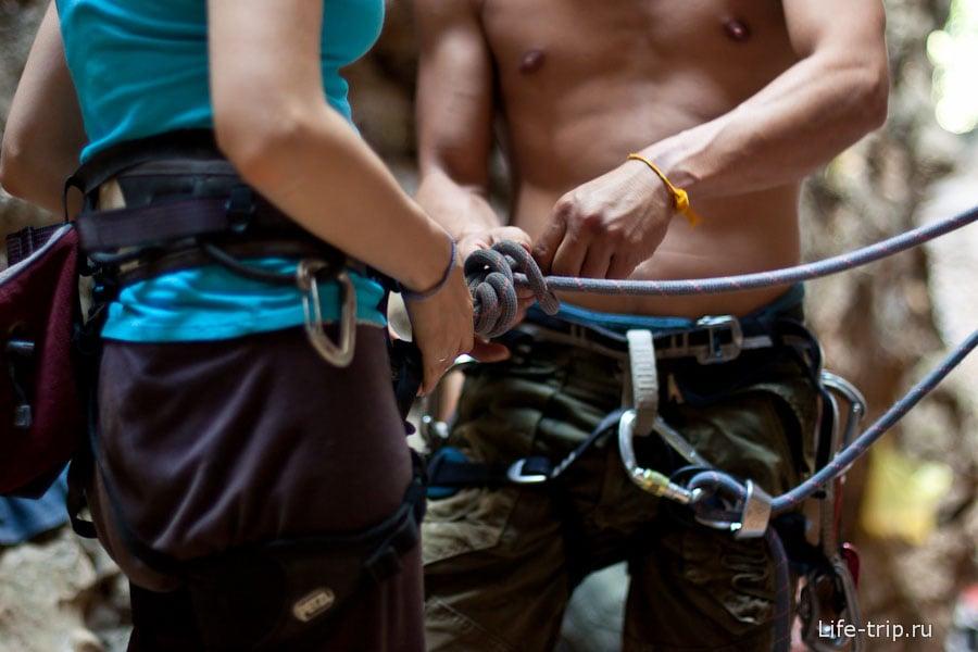Инструктор показывает, как крепить карабин к обвязке