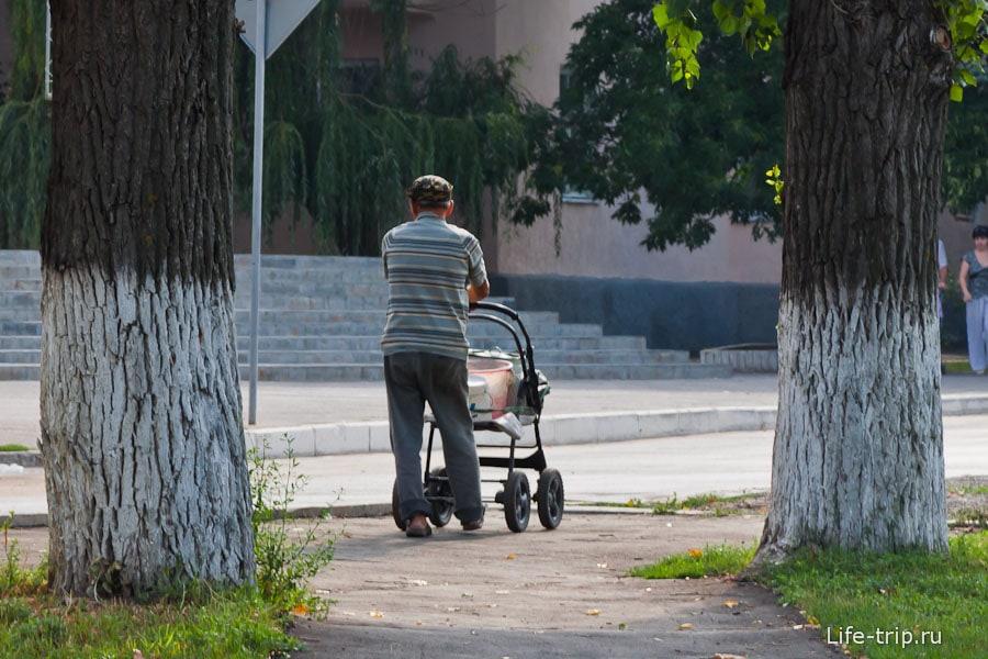 Мужчина везет в коляске ведра