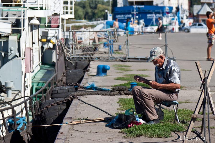 Рыбак в серебристой рубашке на пристани Азова
