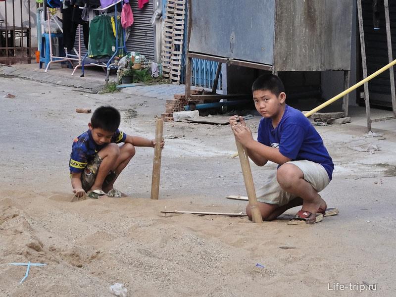 Дети играют с песком и бамбуком