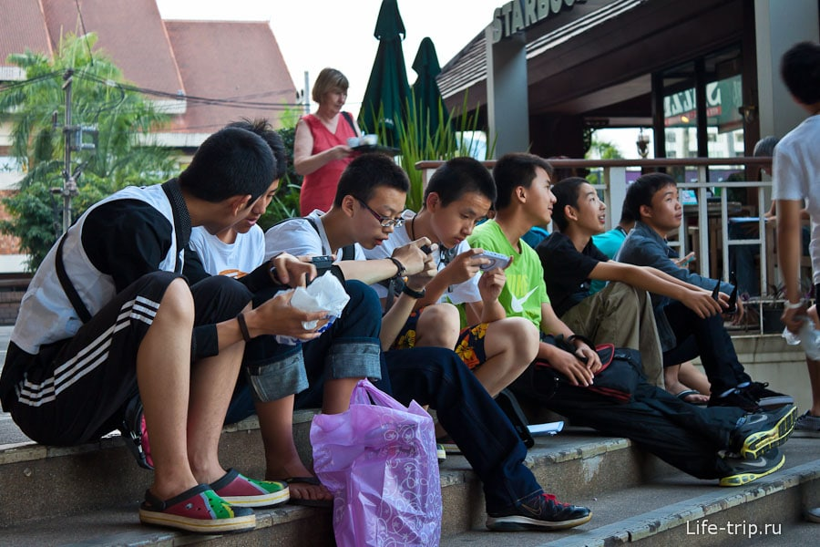 Тайские школьники уткнувшиеся в телефоны