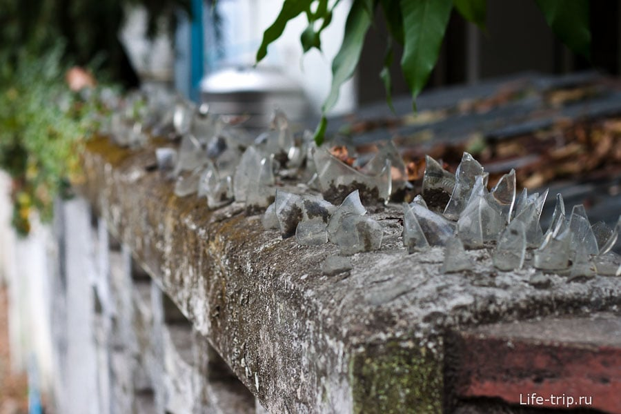 Забор защищенный вмурованными осколками стекла