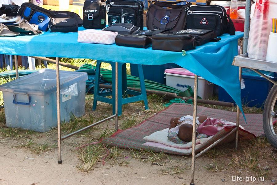 Ребенок спит на рынке под столом