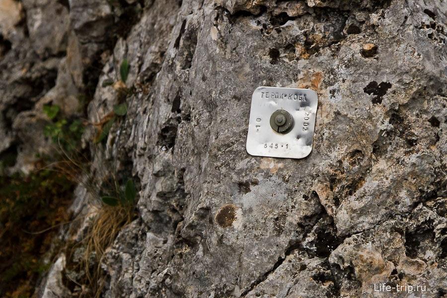 Прибитая бляшка с названием пещеры