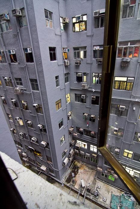 Из окна пробивается свет и видно соседнее здание