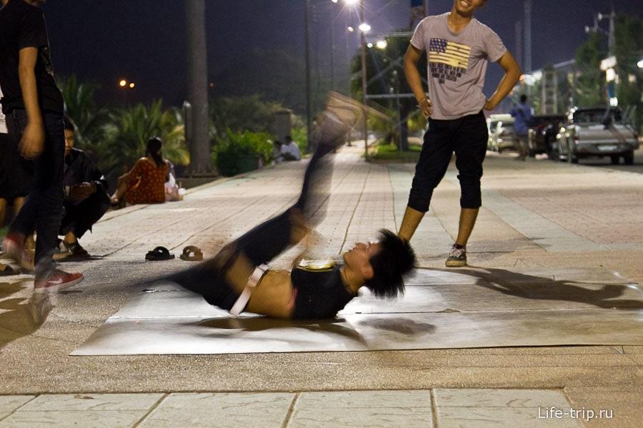 На набережной вечером молодежь танцует брейк