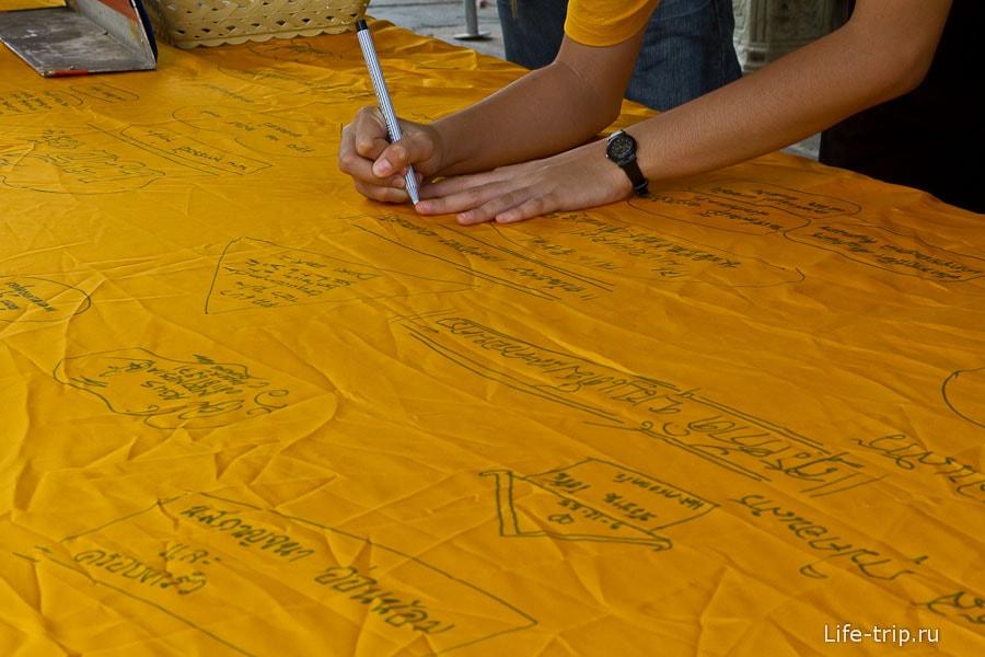 Пишут пожелания на желтой ткани