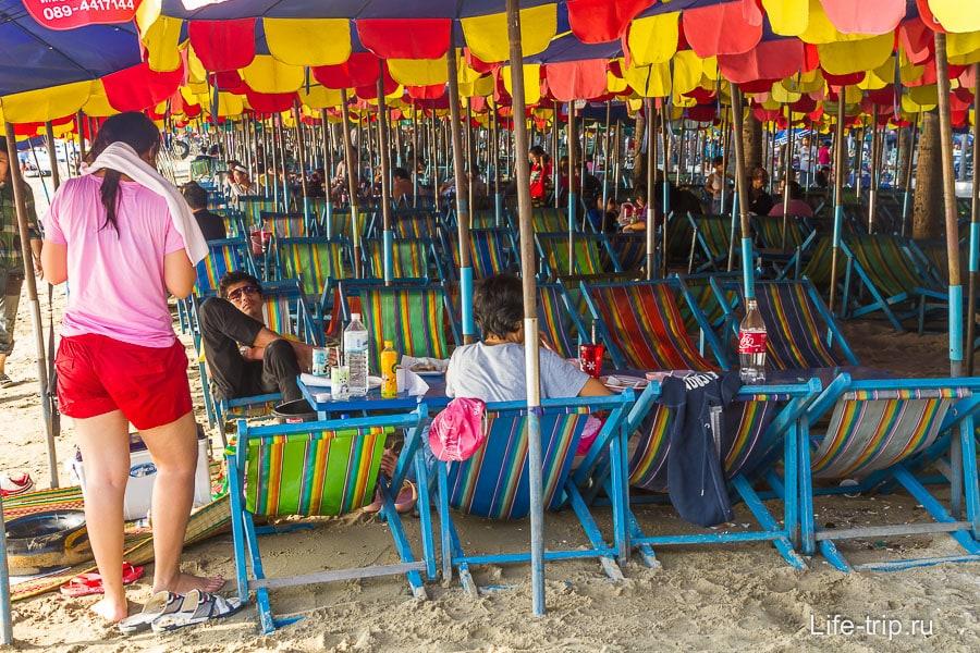 Весь берег кучно заставлен шезлонгам, отдых по-тайски