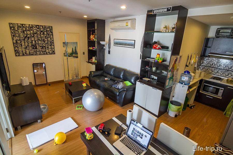 Гостиная с большим телевизором, диваном и обеденным столом
