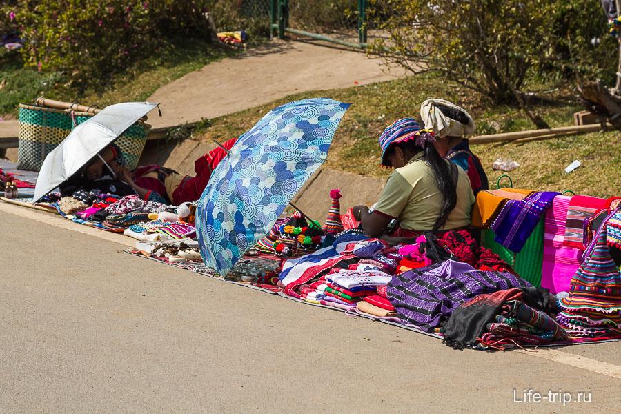 Бирманцы сидят в ряд с зонтиками и что-то продают