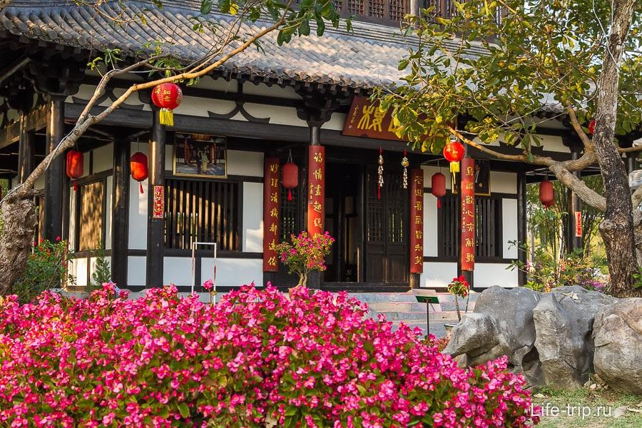 Китайское здание окружено камнями и бонсаями