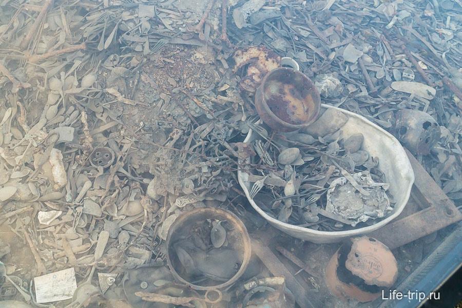 На месте одного из  бараков под стеклом лежат предметы обихода