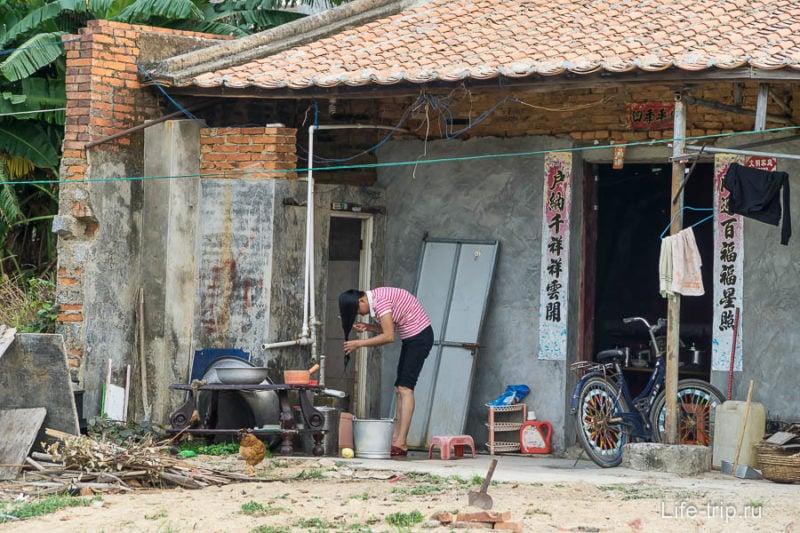 Девушка моет голову в ведре на крыльце своего дома