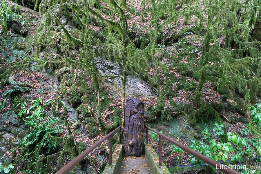Около входа стоит несколько деревянных фигур