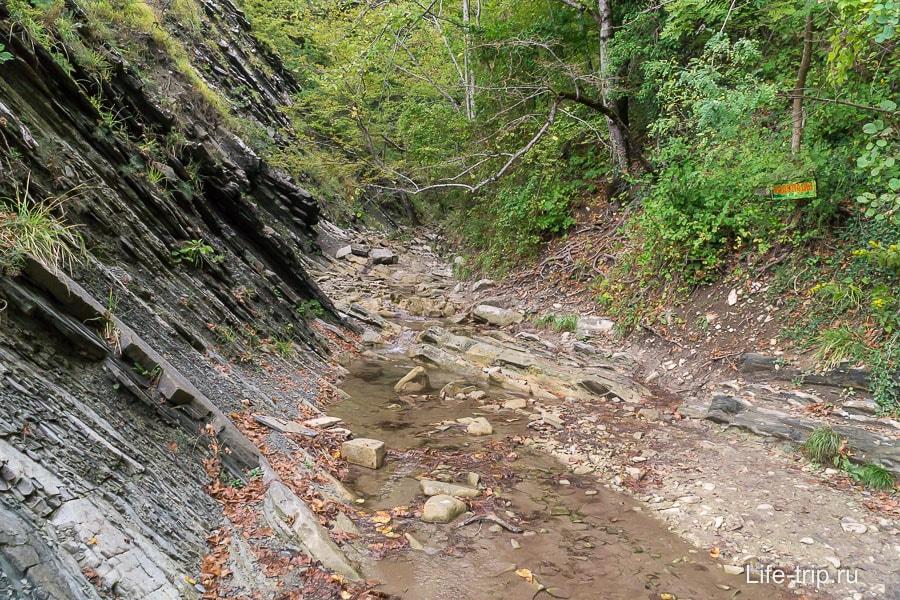 Русло реки продолжается дальше, указатель зазывает продолжить путь