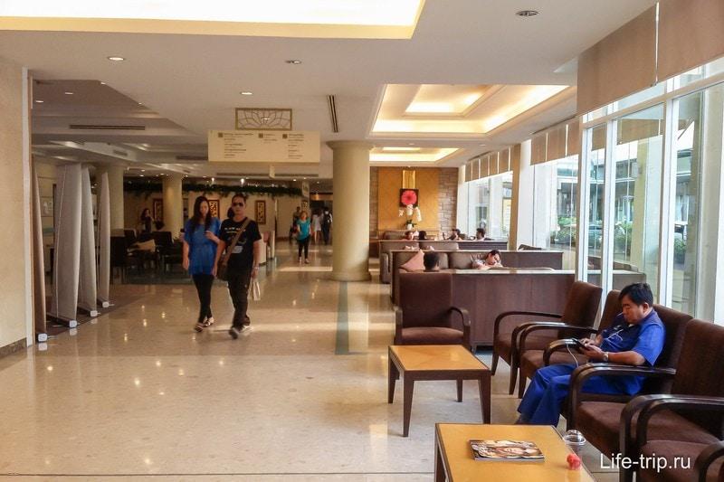 Огромный холл с диванчиками, нескольким кафешками и магазинчиками