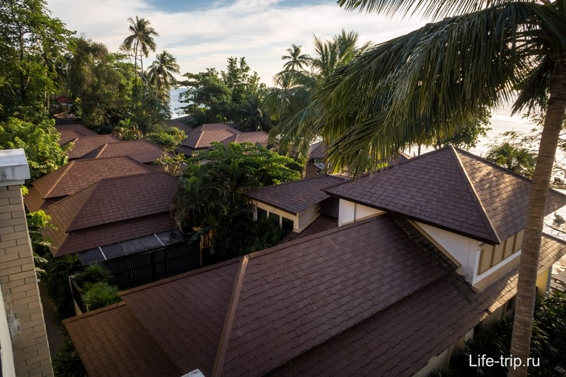 Видны крыши, море и бассейн