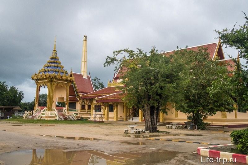 Очень тайская фотка: крематорий, храм, столик под деревом, лужи и лежачий полицейский на земляной дороге.