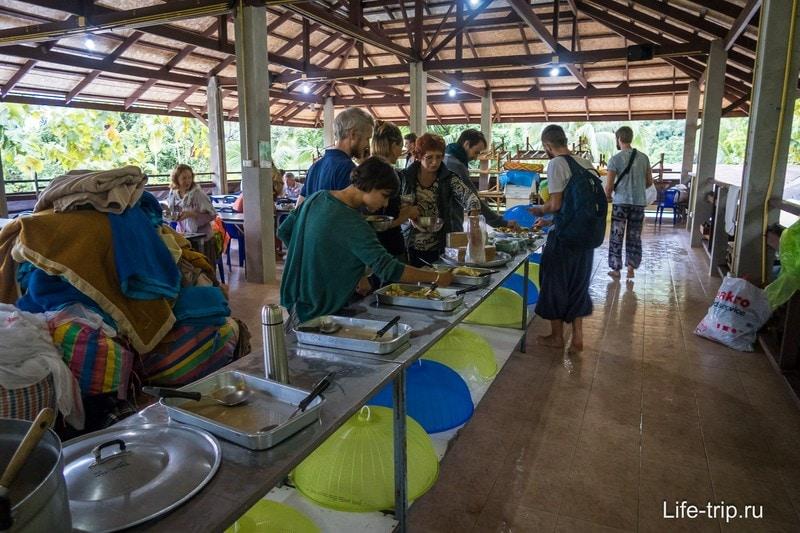 Обеденный холл и стол с едой, куда все подходят по очереди