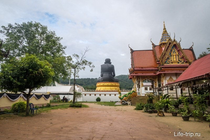 Издалека видно статую монаха на лодке