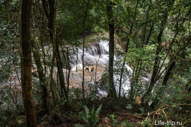 Конец тропы, таким вы увидите водопад Кхун Си сквозь деревья