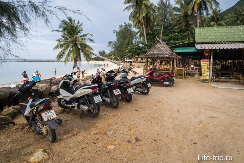 Сразу после поворота, вдоль берега организована парковка для скутеров и машин, но можно проехать и дальше