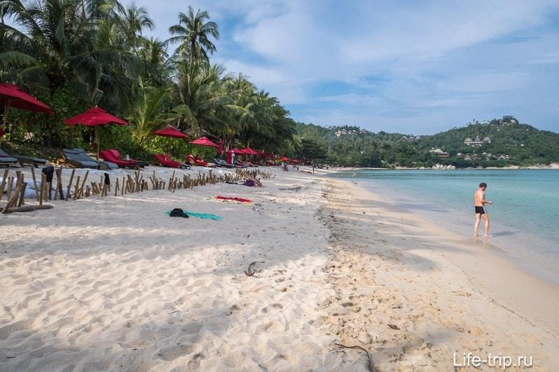 Слева пляж тоже упирается в мыс. Позади, на песке - импровизированный забор соседнего резорта.