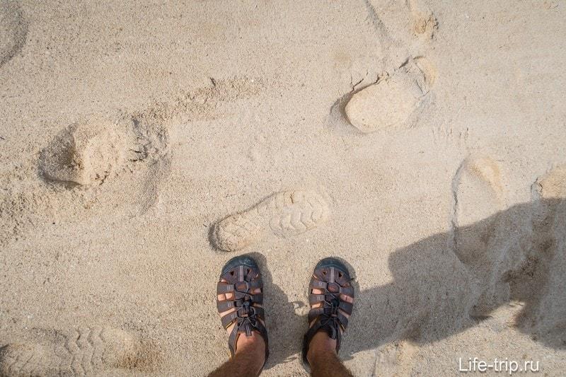 Песок ближе к берегу более-менее нормальный. У воды - гряда камушков и ракушек.