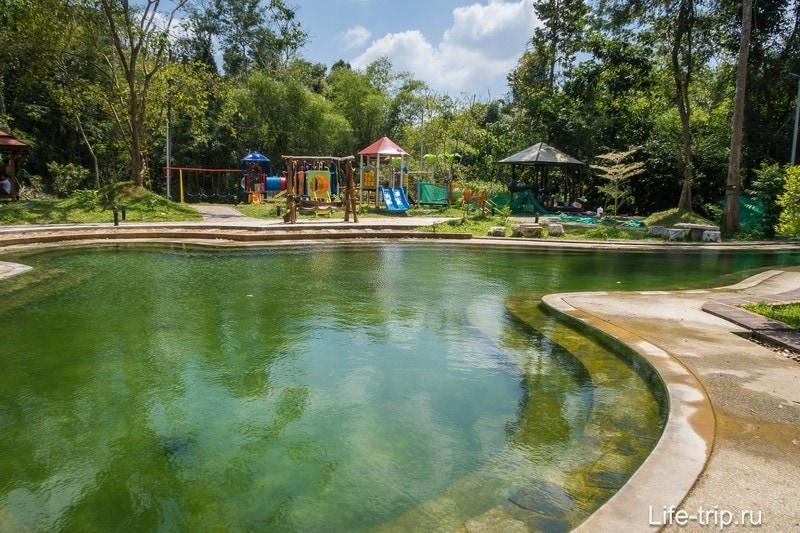 Позади бассейна видно детскую площадку.
