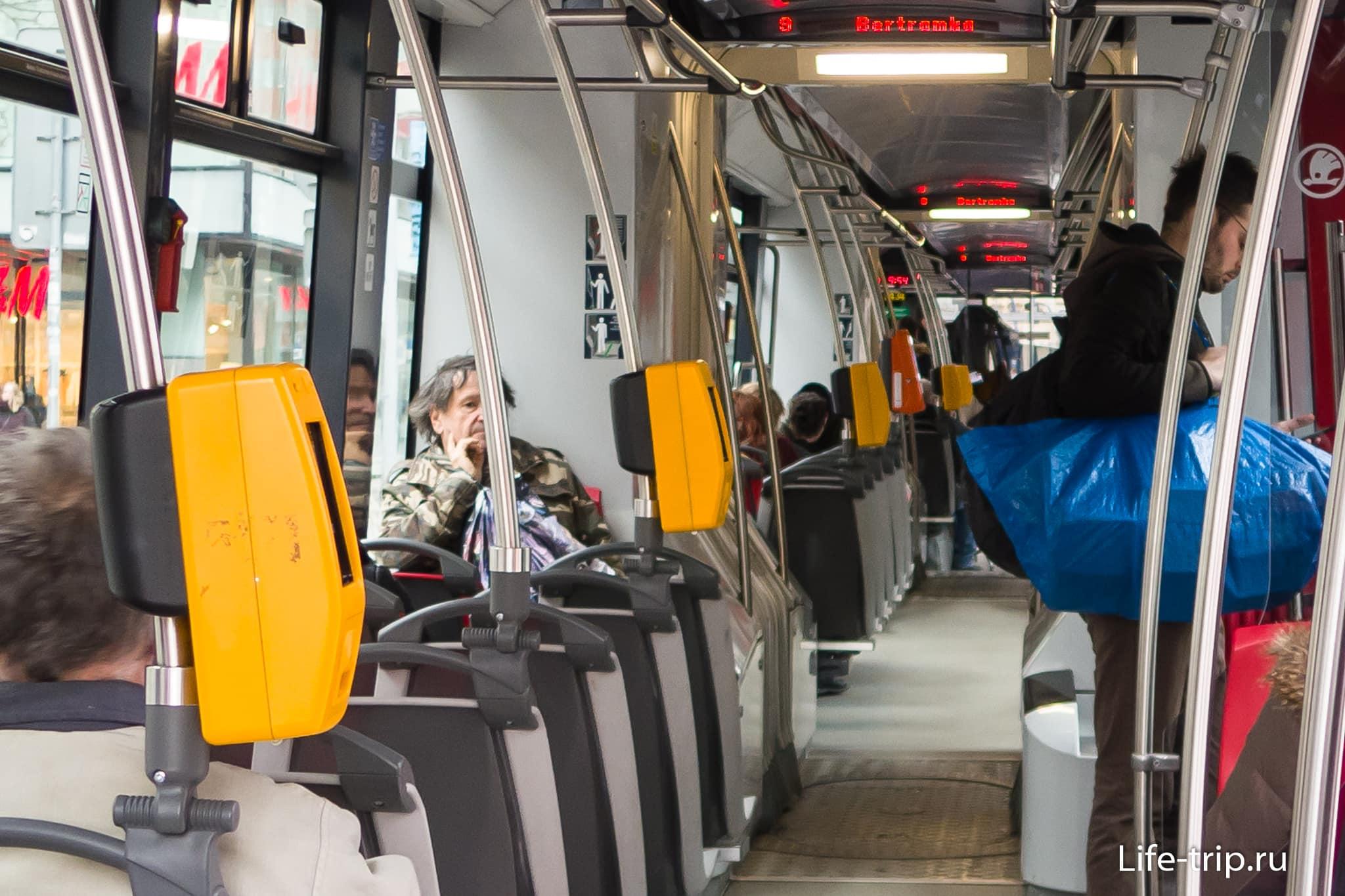 Валидаторы в трамвае – жёлтые, и видно вдалеке оранжевый терминал бесконтактной продажи
