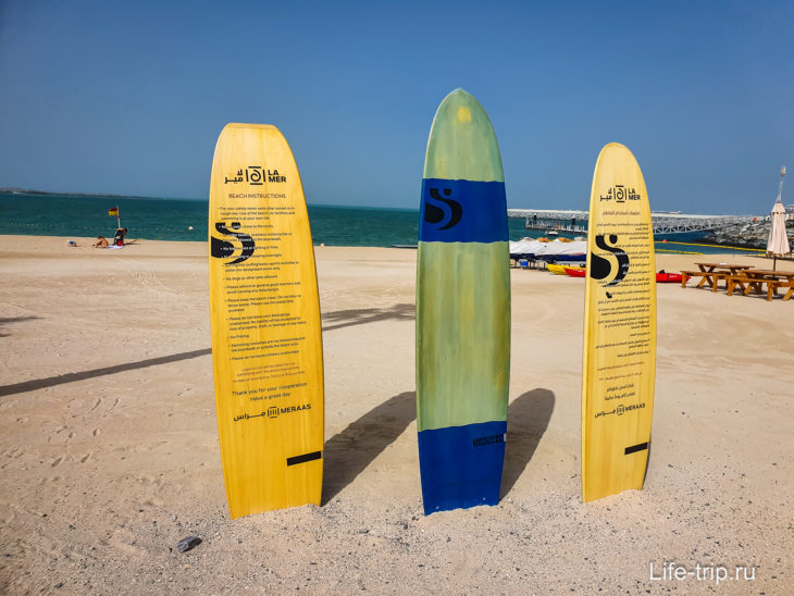 На этих серфах написаны правила поведения на пляже La Mer и телефон полиции
