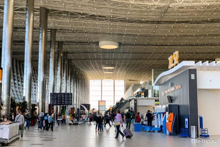 Общий зал: справа – стойки регистрации, в центре – эскалаторы в зону вылета, дальше – выходы в зоне прилёта