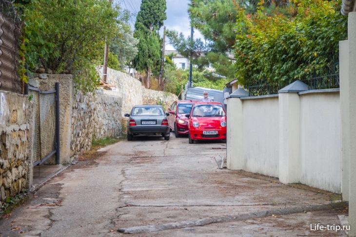 Красные машины припаркованы. Серая - протискивается на выезд