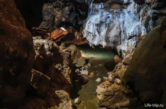 В глубине пещеры тропа идет вдоль русла подземной реки
