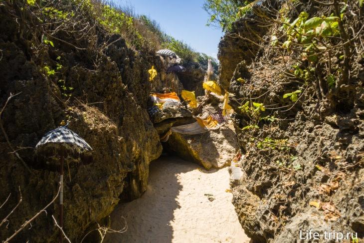 Слева под скалой виден темный треугольник- это проход к пляжу
