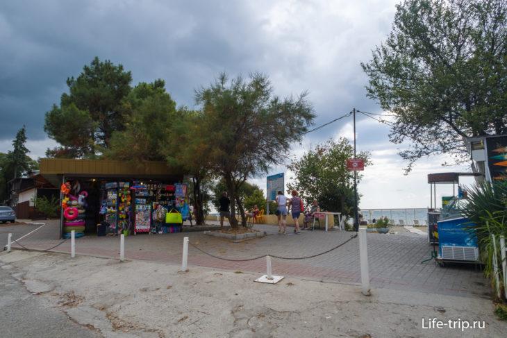 У входа стоят ларьки с пляжными товарами